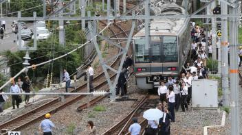 TOPSHOT - Passengers from a train walk along railroad tracks following an earthquake in Osaka on June 18, 2018. - A strong quake hit western Japan early June 18, but there were no immediate reports of major damage or risk of tsunami waves, officials said. (Photo by STR / JIJI PRESS / AFP) / Japan OUT (Photo credit should read STR/AFP/Getty Images)