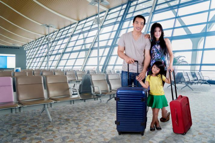 happy-family-smiling-airport-portrait-camera-standing-terminal-their-suitcase-87761414.jpg